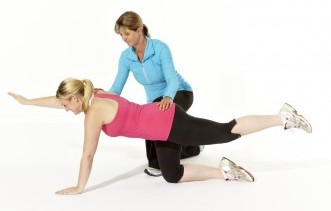 Physio helping client with exercise